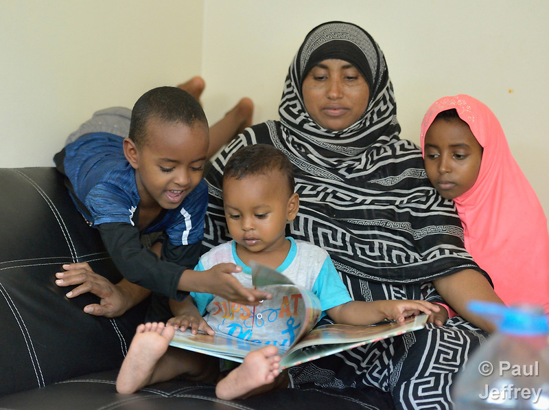 Mekiya Kebir and her children, recently arrived refugees from Eritrea, explore a book in their apartment in Lancaster, Pennsylvania. They got the book and other educational materials from Church World Service, which resettles refugees in Pennsylvania and other locations in the United States. Photo by Paul Jeffrey for Church World Service. (Paul Jeffrey)