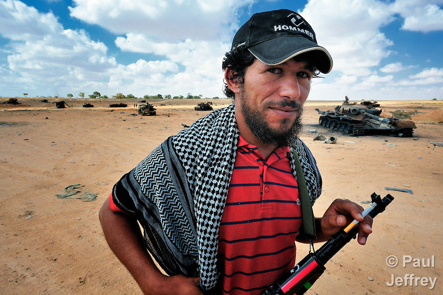 A rebel fighter in Misrata, Libya. Behind him are tanks of troops loyal to strongman Moammar Gadhafi which were destroyed in NATO air strikes.