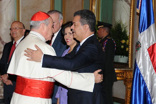 El cardenal Nicolás López y Leonel Fernández se abrazan.