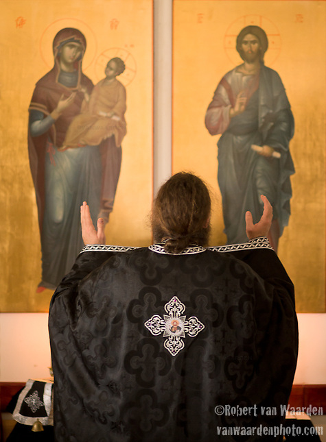 Father Iustin Petre prays during service. (Robert van Waarden)