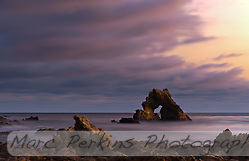 Clouds blow over the arch rock visible offshore at Little Corona.  Captured after sunset on a gorgeous day, the long exposure softens the ocean waves into a silky smooth, almost misty, layer. (Marc C. Perkins)