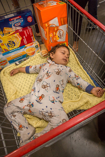 One year old Jovonni dreams of Goldfish while his mother shops at Costco in Vallejo, CA. (Clark James Mishler)