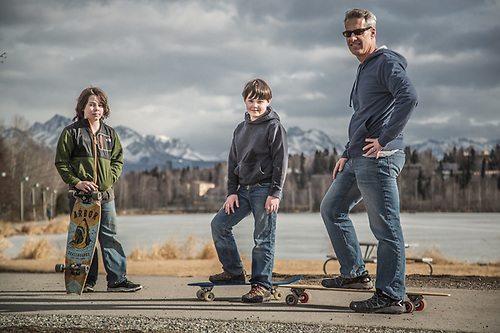 "Stay at home dad Sean Johnson with his sones Brynn (9) and Aidan (11) near Westchester Lagoon.  ""This is our first time out on our boards…its a bit early as there is still some ice on the trail."" (© Clark James Mishler)"