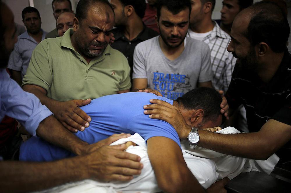 CIUDAD DE GAZA (FRANJA DE GAZA) 18/07/2014.- Un hermano del palestino Mohammed Abu Taweela llora sobre su cuerpo en el depósito de cadáveres de Al Shifa durante su funeral en la ciudad de Gaza (Franja de Gaza), hoy, viernes 18 de julio de 2014. Abu Taweela falleció por los disparos procedentes de un tanque israelí durante la noche de ayer. EFE/Mohammed Saber