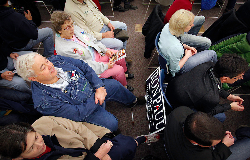 Ron Paul supporter Robert McNamara, left center, of Spillville, Iowa sits with a newly-claimed campaign sign while waiting for Congressman Paul to arrive to a campaign stop in Waverly on December 9. (Christopher Gannon)