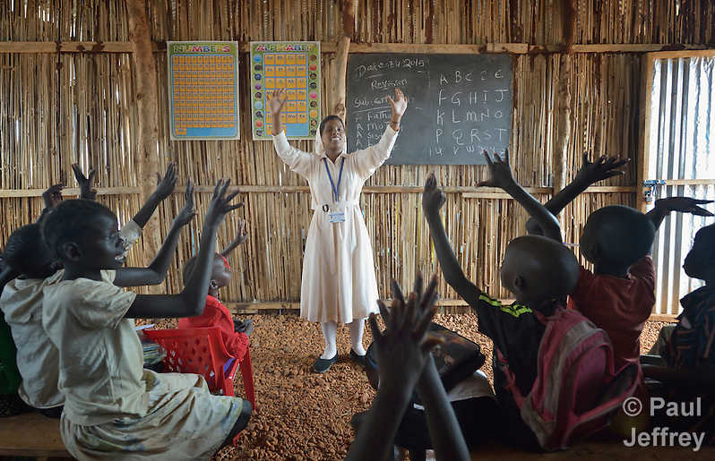 Sister Mariya Soosai, a member of the Daughters of Mary Immaculate, leads a group of children in an arithmetic class in a camp for internally displaced families inside a United Nations base in Juba, South Sudan. Some 34,000 people have sought protection here since violence broke out in December 2013. More than 112,000 people currently live on UN bases in the war-torn country, most of them afraid of tribally targeted violence. Ten DMI sisters from India work in the Juba camp, providing counseling and psycho-social support for women and children, teaching children in makeshift schools, and providing food to hungry families. (Paul Jeffrey)