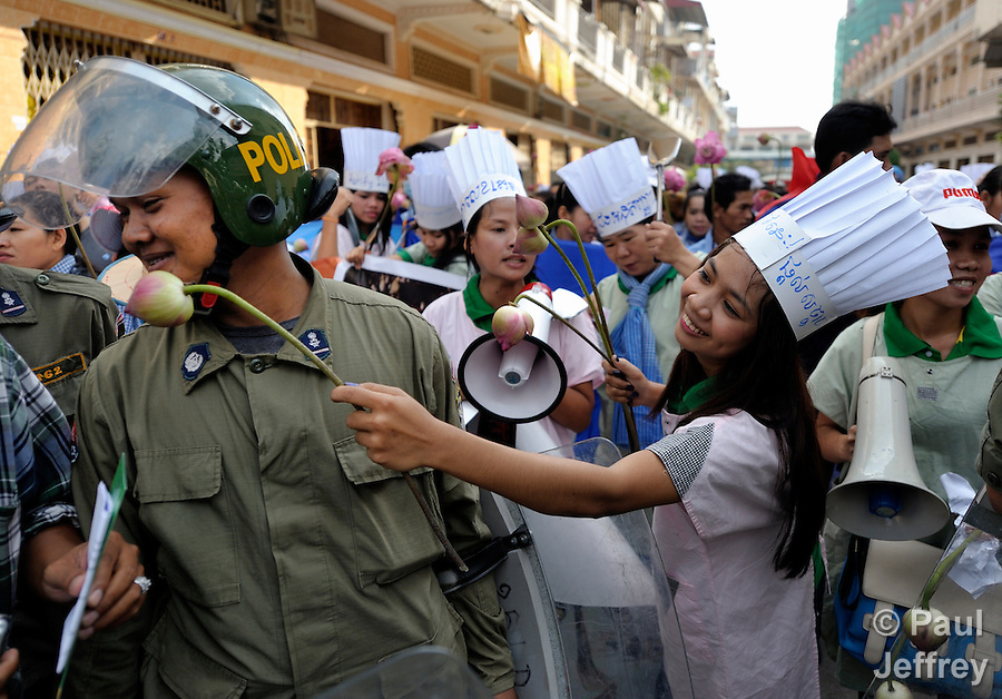 A protester offers a flower to a police officer on International Human Rights Day, when informal sector workers, including domestic workers and tuk-tuk drivers, attempted to protest in Phnom Penh on December 10, 2012. They were calling for the Cambodian government to ratify ILO Convention 189 guaranteeing the rights of domestic workers, and planned to take their request to the prime minister's office, but police stopped them far short of their goal. Protesters called for police pay to be increased, and offered water and flowers to the police who were blocking their passage.