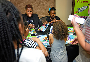 "Young author Nia Mya Reese, right, signs copies of her book, ""How to Deal with and Care for Your Annoying Little Brother,"" April 21, 2018, at Homewood Public Library in Birmingham, Ala. Her mother, Cherinita Ladd-Reese, left, helped her find a publisher for the book and assists with public speaking engagements. Nia Mya, now 9 years old, was 7 when the book was published. (Photo by Carmen K. Sisson/Cloudybright) (Carmen K. Sisson/Cloudybright)"