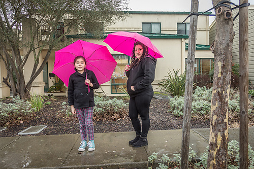 Brenda Chairez with her daughter, Briseida, pause on Washington Street during a rain storm  in Calistoga (Clark James Mishler)
