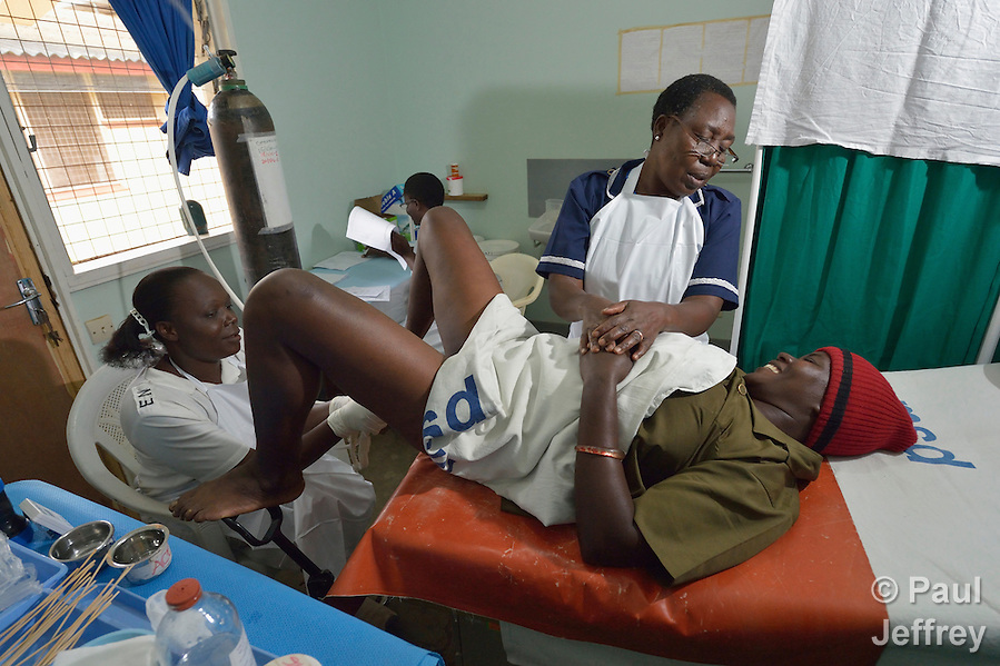 Nurse Moureen Mbise comforts Sherida Katibu as Nurse Joyce Agutu uses a cryoprobe to do cervical cryotherapy on her in the Shirati Hospital in Shirati, Tanzania. Nurse Elizabeth Peter does paperwork in the background. (Paul Jeffrey)