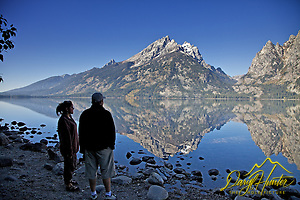 A couple enjoy the grandeur of a Grand Teton reflection upon the still waters of  Jenny Lake in Grand Teton National Park. (© Daryl L. Hunter - The Hole Picture/Daryl L. Hunter)