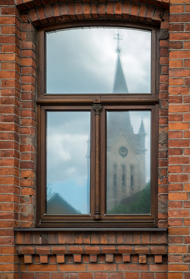 LATVIA, CESIS - CIRCA JUNE 2014: View of tower of the St. John's Church reflected in a window of an old buildinig in Cesis in Latvia. (Daniel Korzeniewski)