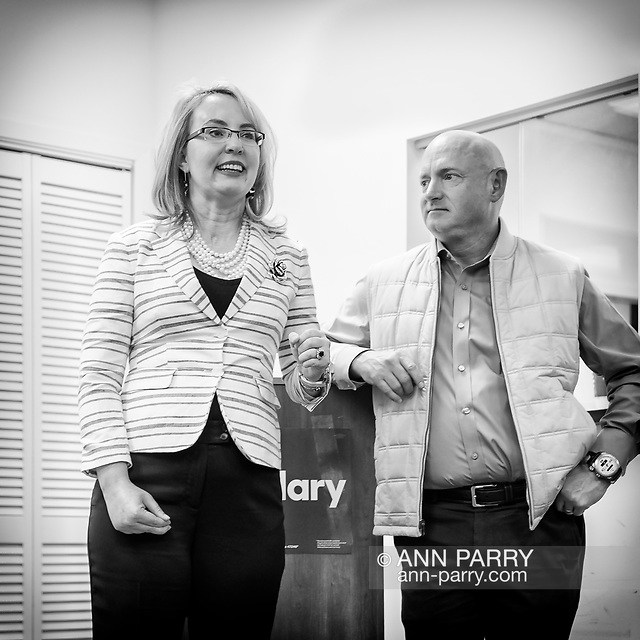"""""""Garden City, New York, USA. April 17, 2016. GABBY GIFFORDS, former United States Congresswoman - as her husband MARK KELLY, former NASA astronaut looks on - speaks about the importance of GOTV, Getting Out The Vote for Hillary Clinton - including because of Clinton's strong position on stricter gun control legislation - at the Canvass Kickoff at the Nassau County Democratic Office in Garden City. Giffords survived an assassination attempt near Tuscon, Arizona, during her first 'Congress on Your Corner' event in January 2011. Kelly was a NASA astronaut. (© 2018 Ann Parry/AnnParry.com)"""