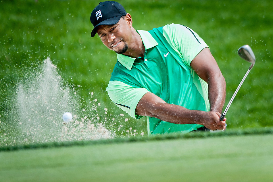Tiger Woods blasts out of the greenside bunker on the 3rd hole during the first round of the Quicken Loans National golf tournament on Wednesday at Congressional Country Club in Bethesda, Maryland. This marked  Woods' return to competition for the first time in three months after having surgery just a week before the Masters in April of this year. (Pete Marovich/Corbis)