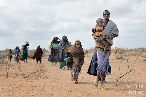 Newly arrived refugees carry their belongings through the Dadaab camp in northeastern Kenya. Already the world's world's largest refugee settlement, Dadaab has swelled in recent weeks with tens of thousands of recent arrivals fleeing drought in Somalia. The Lutheran World Federation, a member of the ACT Alliance, is manager of the camp, and in July opened a new extension to begin housing the newest refugees.