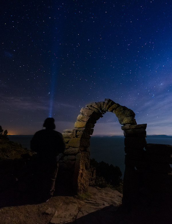 PUNO, PERU - CIRCA OCTOBER 2015: Man looking the sky and stars by a typical arch of the Island of Taquile in Lake Titicaca. (Daniel Korzeniewski)