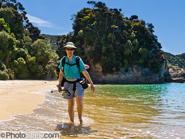 A tramper hikes on sandy Mutton Cove Beach, along the Abel Tasman Coastal Track, Abel Tasman National Park, South Island, New Zealand. Book huts using the Great Walk reservation system. (© Tom Dempsey / Photoseek.com)