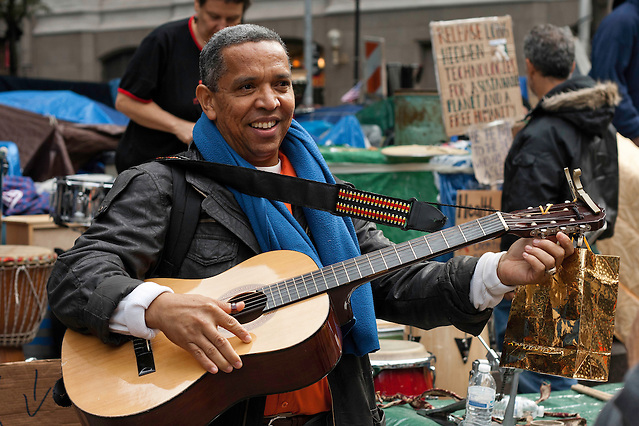 A guitar player tuning up before a performance at the Occupy Wall Street movement in Zuccotti Park. October 21, 2011. (Emon Hassan)