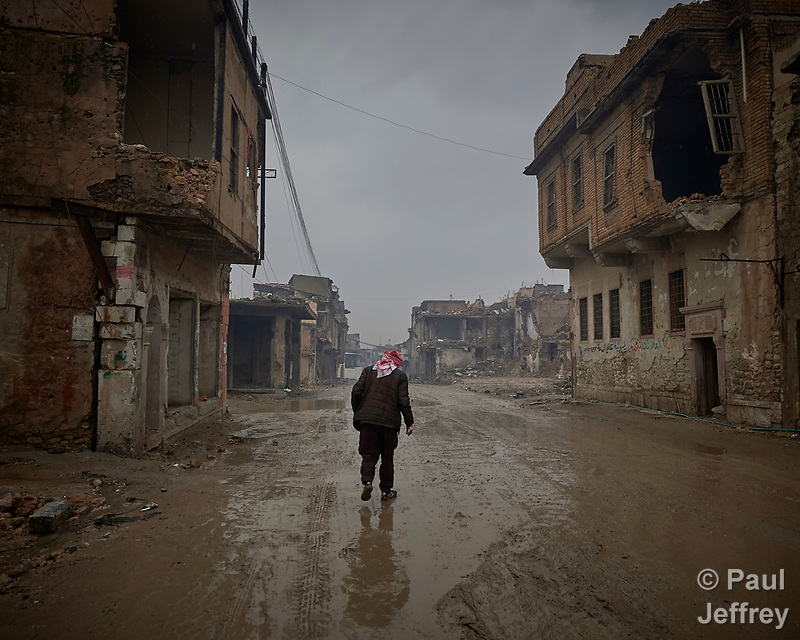 Qasim Yahia Ali, 75, walks along a rainy street in the old city of Mosul, Iraq. His house was destroyed during the 2017 Battle of Mosul, which led to the defeat of the Islamic State group, also known as ISIS. During control of the city by the Islamic State, he earned money by making clandestine liquor. In the wake of the war, he has moved back into the old city and lives in the ruins. (Paul Jeffrey)