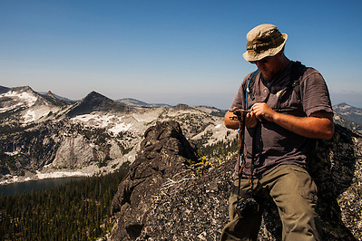 A male adult hiker checks his GPS position a few feet from the top of Harrison Peak in Northern Idaho's Selkirk Range. (Benjamin Chase)