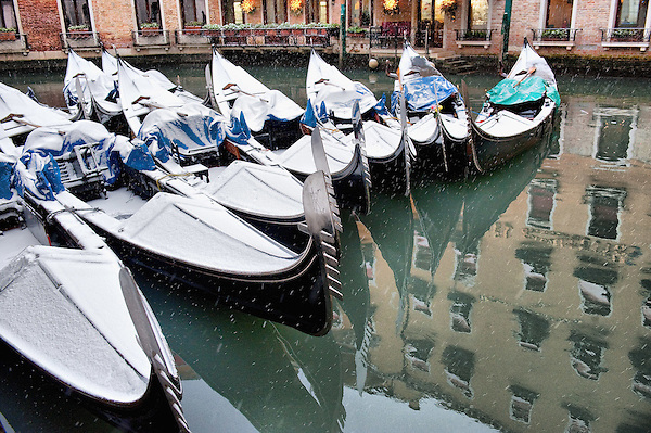 VENICE, ITALY - DECEMBER 17: Gondolas covered with snow rest in Bacino Orseolo on December 17, 2010 in Venice, Italy. Snow has fallen across much of Europe today and is expected to continue over the weekend, causing traffic chaos and disrupting Christmas deliveries. (Marco Secchi)