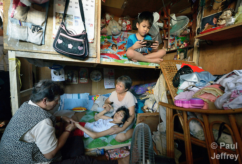 Rafaela Valencia exercises the legs of Susan Dison's 15-year old daughter Susein, as Dison's 7-year old son Apo plays an electronic game in their crowded home in the Malate neighborhood of Manila. They are members of Kaisahan ng Magulang at Anak na Maykapansanan (Kaisaka), a mothers' group that carries out community based rehabilitation with families which have members with disabilities. Susein has cerebral palsy. (Paul Jeffrey)