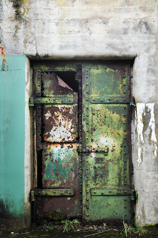 Closed rusty green steel door on concrete bunker tunnel, Artillery Hill, Fort Warden State Park, Port Townsend, Washington, USA (Brad Mitchell)