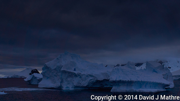 Iceberg at Night off the North-West Antarctica Peninsula. From the deck of the Hurtigruten MS Fram on New Year's Eve. You want to stay clear of the icebergs at night. Image taken with a Leica T camera and 18-56 mm lens (ISO 100, 23 mm, f/8, 1/500 sec). Raw image processed with Capture One Pro 8, and Photoshop CC. (David J Mathre)