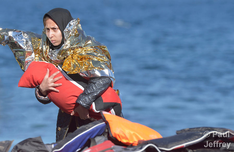 A refugee woman clutches her baby after landing on a beach near Molyvos, on the Greek island of Lesbos, on November 2, 2015. Part of a boatful of refugees that arrived from Turkey, she and her family were received by local and international volunteers, then proceeded on their way toward western Europe. The boat was provided by Turkish traffickers to whom the refugees paid huge sums to arrive in Greece. (Paul Jeffrey)