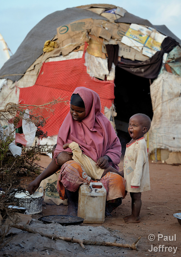 Kadija Abdi Wadadow nurses one child while her son Bashir Aliyon yawns in the Dadaab refugee complex in northeastern Kenya. Fleeing violence and drought, hundreds of thousands of Somali refugees have made Dadaab the largest refugee settlement in the world. (Paul Jeffrey)