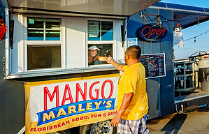Morgan Ryffe gives change to a customer at Mango Marley's, Oct. 4, 2019, in Mexico Beach, Florida. The restaurant was damaged during Hurricane Michael in October 2018, so they are operating out of a food truck and serving a limited menu until the restaurant can be repaired. (Photo by Carmen K. Sisson/Cloudybright) (Carmen K. Sisson/Cloudybright)
