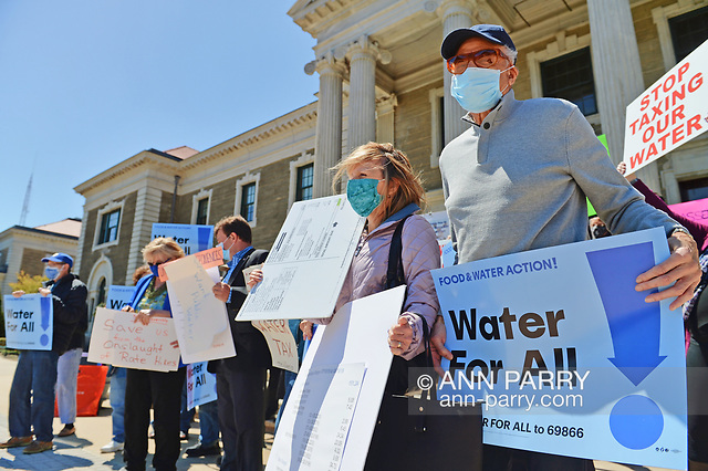 """""""Mineola, NY, USA. April 26, 2021. At rally, activists hold signs saying STOP TAXING OUR WATER, and Water for ALL! Faced with a 26% rate increase from New York American Water going into effect May 1, 2021, activists and residents who are NYAW customers rally. (© 2021 Ann Parry/AnnParry.com)"""