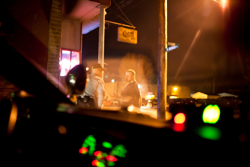 Police in Sabina, Ohio, speak with a well known local youth outside one of the rougher bars in town. (Quinn Ryan Mattingly)