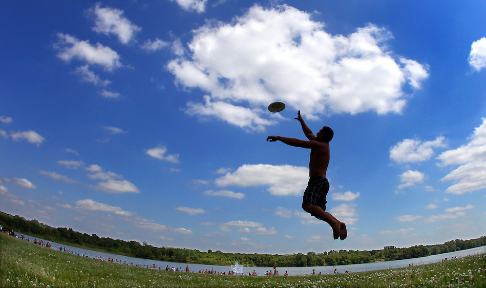 A cloud-dotted summer sky sprawls over Dustin Medearis of Pleasant Hill, leaping for a Frisbee while playing catch at Raccoon River Park on June 29. (Christopher Gannon/The Register)