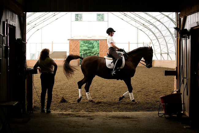 08/27/2013 -- GEORGETOWN, Mass. -- Phyllis LeBlanc, President and CEO of Salem, Mass.-based chocolate company Harbor Sweets, paces her dressage horse Chiron through a workout as her trainer Cindi Wylie checks her form at Quarterline Dressage in Georgetown, Mass., on Aug. 27, 2013. LeBlanc, who has 30 years of experience as a competitive dressage rider, says she finds comfort in the process of preparing a dressage horse. Riding involves core and leg strength, as well as fine motor control to maintain control of the horse, which Wylie compares to skiing. (Kelvin Ma for the Wall Street Journal) (Kelvin Ma)