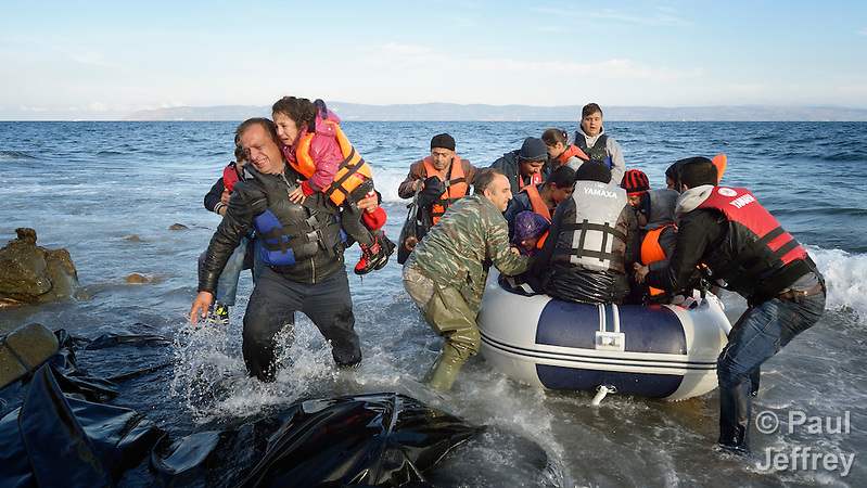 When he landed on the Greek island of Lesbos on October 30, 2015, Nabil Minas, a refugee from Syria, carried his children through the water--including the daughter he carries on the left--and left them on the shore, then fell on his face and kissed the ground. A Christian, he crossed himself and covered his face with his hands, weeping with joy. Minas and his family came in the boat from Turkey, paying an exorbitant amount to traffickers who provided the transport. (Paul Jeffrey)