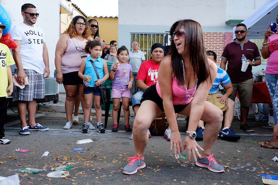 MIAMI - MARCH 9, 2014: Portrait of woman dancing in the streets during the 37th Calle Ocho festival, an annual event that takes place over Eighth Street in Little Havana featuring plenty of music, food, and  it is the biggest party in town that celebrates hispanic heritage. (Daniel Korzeniewski)