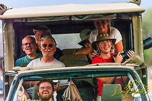 On safari in Kruger National Park, a group of happy photographers look on amused as I shoot their vehicle while walking backwards and nearly plowing over some unseen tourists on the road behind me. Much to their disappointment, I missed the tourists. (Daryl L. Hunter)