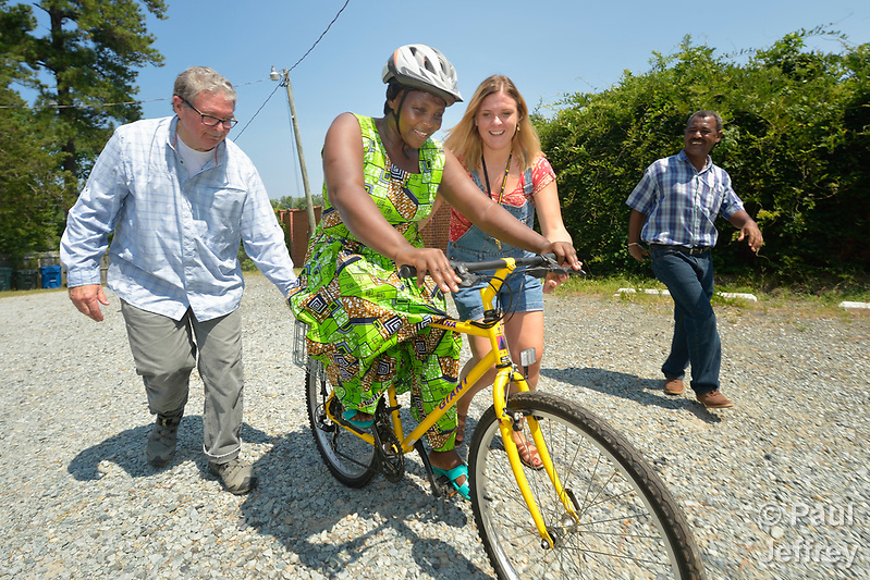 Evanis Gatunzi, a refugee from Rwanda, rides a bike for the first time in Durham, North Carolina, on July 22, 2017. She's helped by Greg Garneau, a volunteer who coordinates the refugee bike program for the Durham Bicycle Co-op, and Monique Lohmeyer, a case manager for Church World Service. In the background, Yosef Birhane, a refugee from Eritrea, cheers her on. Church World Service resettles refugees in North Carolina and throughout the United States. Photo by Paul Jeffrey for Church World Service. (Paul Jeffrey)