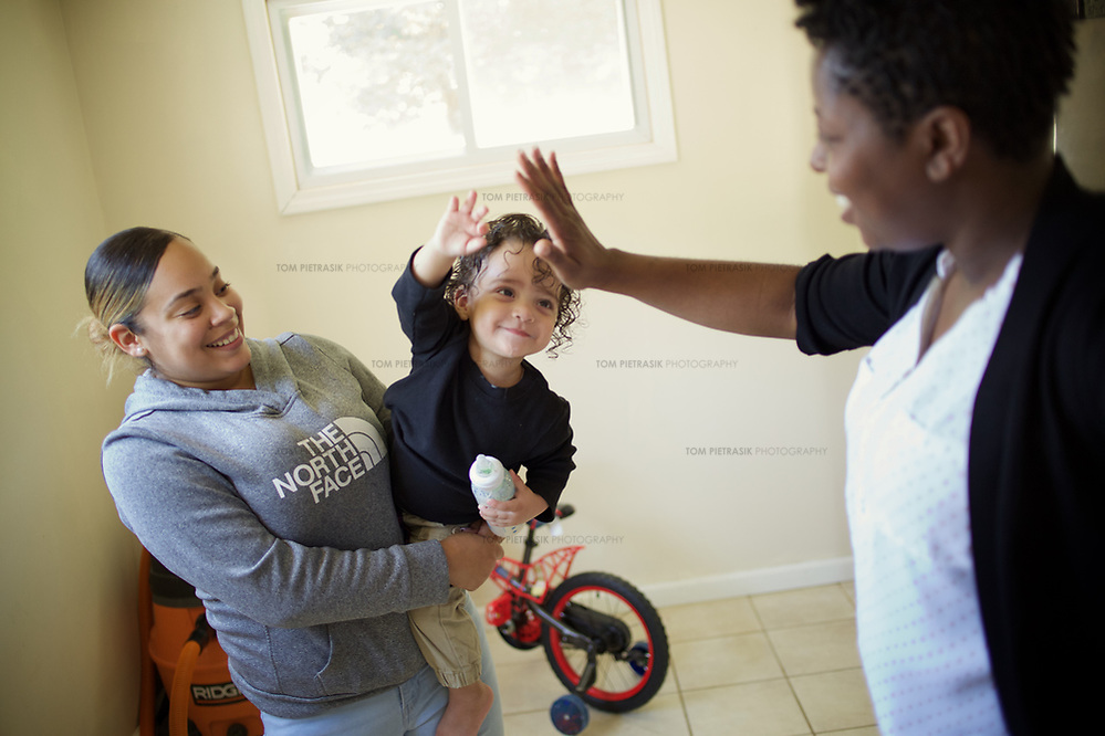 Supportive Housing program case worker, Melissa (in white shirt) spends time with client Irma and Irma's son, Julio, age 18 months. Irma's house was provided with the assistance of the Supportive Housing program in Connecticut. Melissa has provided support to Irma for over two years. Irma, age 24, left home at the age of nine after she and her brother suffered abuse at the hands of their step father. After several years in the care of foster homes and living homeless, Irma became pregnant at age 15. By the age of 23, Irma had lived through periods of homelessness and had become mother to four children with two different men, both of whom were abusive. Six months into her fourth pregnancy, Irma's partner threw her down the stairs and she went into premature labour. Medical staff told Irma that she would miscarry but her youngest son, Julio survived after spending the first six months of his life in hospital. The sustained involvement of medical professionals in Irma's life alerted the Supportive Housing program to her situation. Case worker Melissa began working with Irma, offering support, advice and providing the funds to purchase items for the care of baby Julio. Melissa made representations to the Department of Children and Families (DCF) to vouch for Irma's character and convince them that Irma should not be separated from her children. Melissa encouraged Irma to go back to school and complete her high school diploma. Supportive Housing provided Irma a housing-voucher so that she could keep her children and live independently of her abusive partner. Irma now lives with her children who have rooms of their own and a back yard in which to play. Julio, now eighteen months, has significant health needs but the relative stability of Irma's life now means she can look to the future with a sense of optimism. She hopes to complete her associates degree in nursing and eventually earn an income that will allow her to live in accommod (Tom Pietrasik)