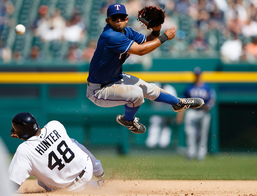May 25, 2014; Detroit, MI, USA; Texas Rangers second baseman Rougned Odor (73) leaps in the air as he makes a throw to first in an attempted double play as Detroit Tigers right fielder Torii Hunter (48) slides into second during the seventh oating at Comerica Park. Mandatory Credit: Rick Osentoski-USA TODAY Sports (Rick Osentoski/Rick Osentoski-USA TODAY Sports)
