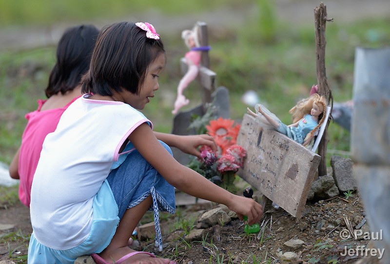 A girl arranges items marking the grave of a friend in a church yard in the city of Palo, in the Philippines province of Leyte, where typhoon Haiyan killed hundreds of people in November 2013. The storm was known locally as Yolanda. (Paul Jeffrey)
