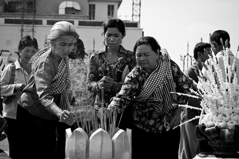 Mourners gather at the site of the stampede tragedy in Phnom Penh, Cambodia to offer their condolences with incense and flowers. Several hundred people perished on November 22nd 2010 when an unknown event sparked panic and caused thousands to flee from Diamond Island in the Mekong River, over the bridge that connects it to the river bank. (Quinn Ryan Mattingly)