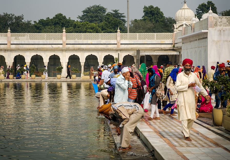 NEW DELHI, INDIA - CIRCA OCTOBER 2016: People worshiping in the pool of Gurudwara Bangla Sahi also known as Sikh house of worship in Delhi. This is oone of the most prominent Sikh gurdwara, often recognized by the pool inside its complex and the golden dome. (Daniel Korzeniewski)