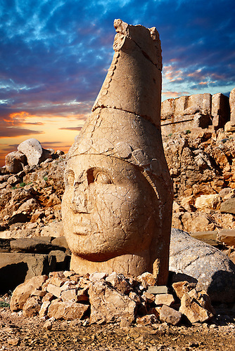Picture & photo of the statues of around the tomb of Commagene King Antochus 1 on the top of Mount Nemrut, Turkey. Stock photos & Photo art prints. In 62 BC, King Antiochus I Theos of Commagene built on the mountain top a tomb-sanctuary flanked by huge statues (8–9 m/26–30 ft high) of himself, two lions, two eagles and various Greek, Armenian, and Iranian gods. The photos show the broken statues on the  2,134m (7,001ft)  mountain. 4 (Paul E Williams)