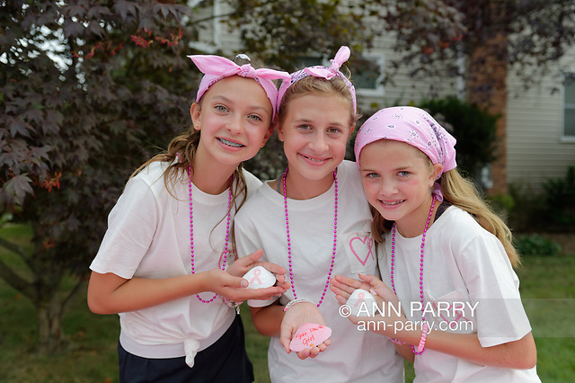 Merrick, New York, U.S. August 15, 2020. Tweens, L-R, ISABELLE, MADDY, and ANNIE FITZPATRICK, hold three of many shells they and friends painted, to raise funds to donate to American Cancer Society Making Strides Against Breast Cancer. The trio formed Lizzie's Army after Annie's 24-year-old sister Lizzie Fitzpatrick was diagnosed with Triple Negative Breast Cancer in late June. (© 2020 Ann Parry/Ann-Parry.com)