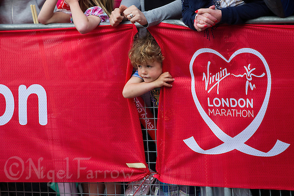 17 APR 2011 - LONDON, GBR - A young spectator peers between banners to watch the runners during the London Marathon .(PHOTO (C) NIGEL FARROW) (NIGEL FARROW/(C) 2011 NIGEL FARROW)