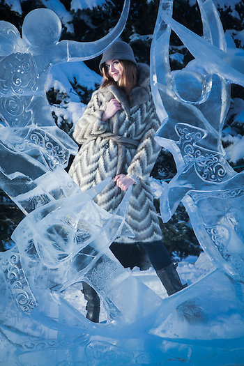 "Taylor Lee models a winter coat from Second Run with the ""Where We Dwell"" ice sculpture by Jenny Rosenbaum and Paul Hanis during the Crystal Gallery of Ice at Town Square, Anchorage, Alaska (Clark James Mishler)"