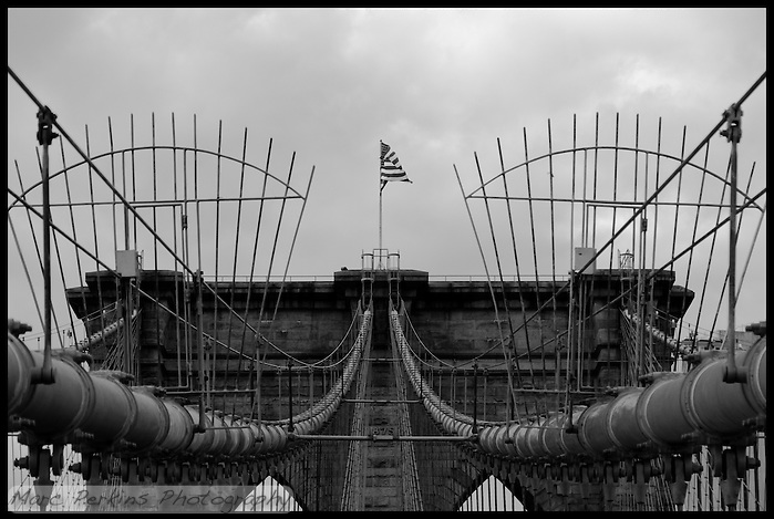 "I loved my visit to New York City, and walking across the Brooklyn Bridge was a highlight.  A strong wind was blowing, and the old brick, wood, and steel just cried out for photography.  This image focuses on the symmetry of cables and towers, with an American Flag blowing right at the viewer from the top of the tower.  I processed this in black and white to emphasize the dark, gritty feel of the old bridge.  The ""1875"" date marker is easily visible in the image.  NOTE: This image has a black border embedded into it for web display; please contact me if you're interested in ordering this image so I can print it without a black border. (Marc C. Perkins)"