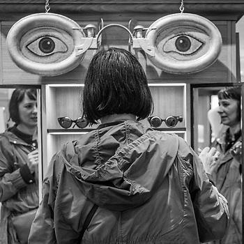 Woman at sunglass quiosque, Paris (Clark James Mishler)